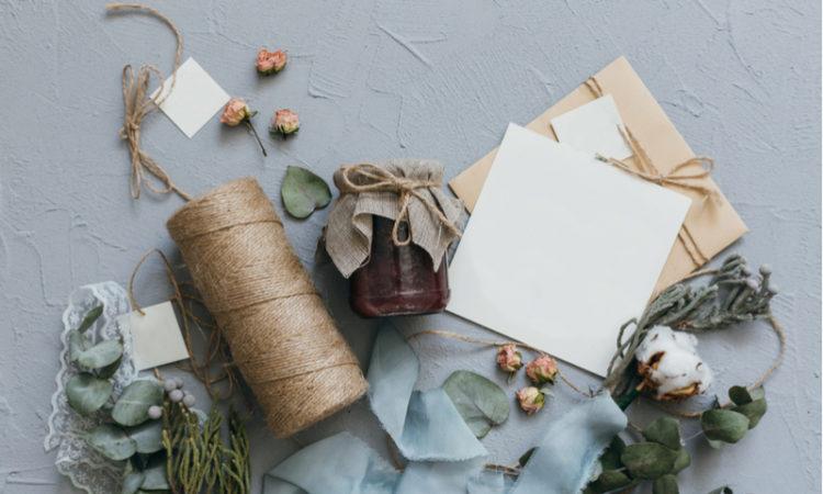 blanke Einladungskarte mit Bastelmaterial auf Tisch