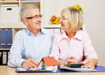 Aelteres Ehepaar macht Kreditvergleich mit Taschenrechner und kleinem Haus
