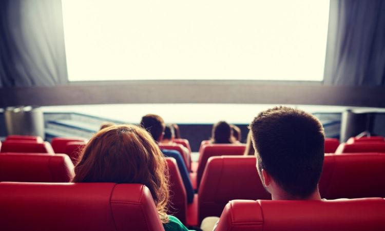 Kinobesucher in Multiplex-Kino sitzen in roten Sesseln und schauen auf weiße Leinwand