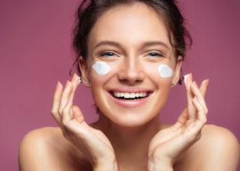 Lachende, junge Frau trägt Gesichtscreme auf ihr Gesicht auf