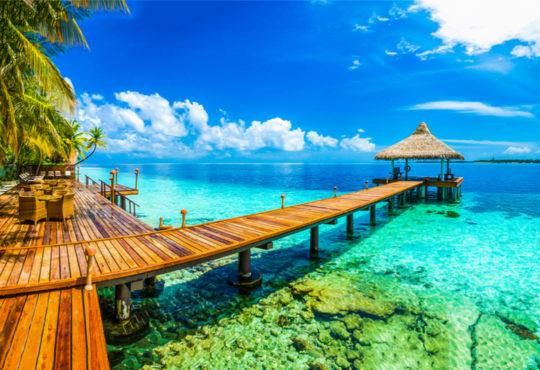 Strand auf den Malediven mit Hotelresort, das ins türksiblaue Wasser hineinragt