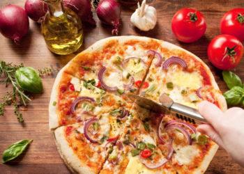 Selbstgemachte Pizza wird mit dem Pizzaroller geschnitten, um sie herum liegen frische Zutaten wie Zwiebeln, Knoblauch, Tomaten, Kräuter