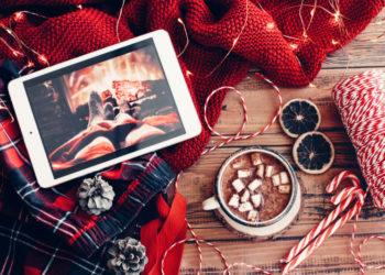 Tablet mit Netflix Weihnachtsfilmmauf rotem Schal mit Tasse Kakao und Weihnachtsprops
