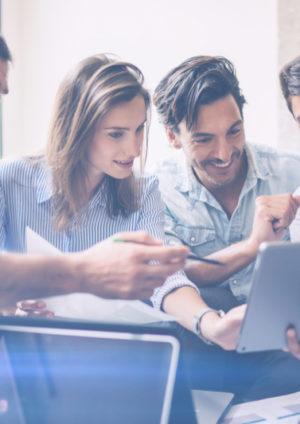 Junge Menschen, die im Online Marketing arbeiten, schauen gemeisnam auf einen Laptop und lachen