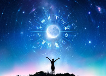 Sternzeichen vor blauem Himmel mit kleiner Menschensilhouette, die sich den Tierkreiszeichen entgegen streckt