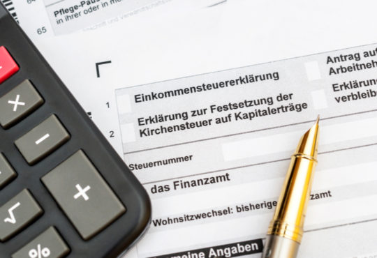 Formular für Einkommenssteuererklärung mit Kugelschreiber und Taschenrechner