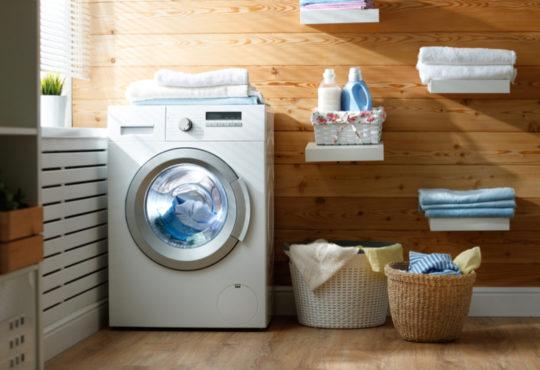 Waschmaschine in der modernen Waschküche mit Wäschekörben und Regalen