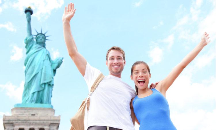 Lachendes Paar posiert neben der Freiheitsstatue in New York