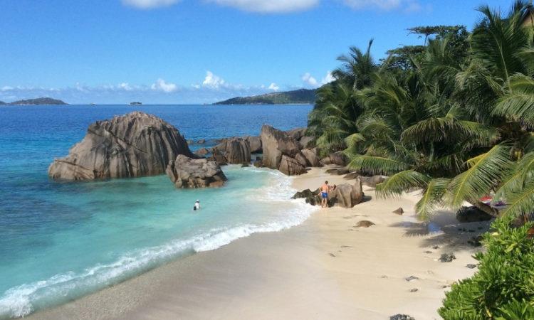 Verlassener, weißer Sandstrand und türkisfarbenes Meer auf den Seychellen