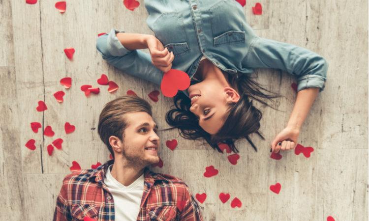 verliebtes Paar, das auf dem Boden liegt umgeben von roten Herzen