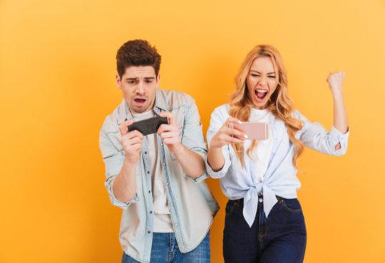 Junge Frau und junger Mann spielen Spiele auf ihren Handys vor gelbem Hintergrund