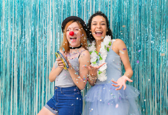 Zwei lachende junge Frauen vor glitzerhintergrund, die Karnevalskostüme tragen