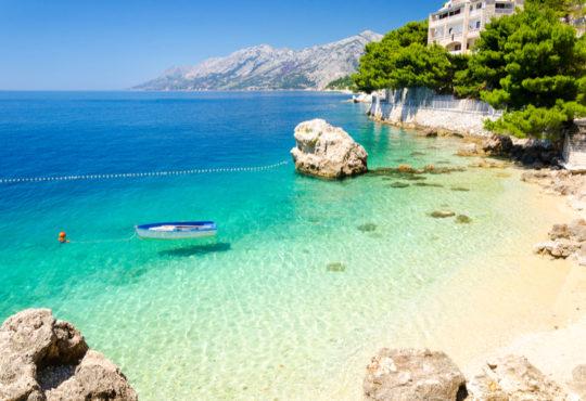 Strand in Kroatien mit Bucht, türkisblauem Meer und Bergen im Hintergrund