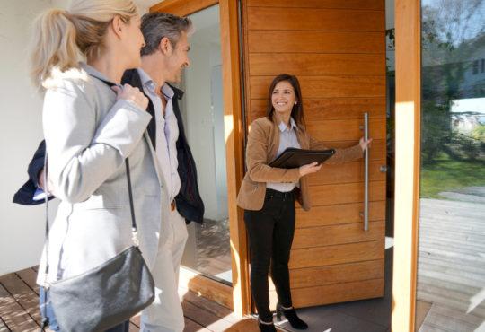 junges Paar betritt ein Haus in Berlin mit Immobilienmaklerin