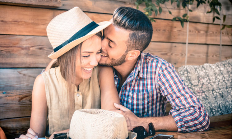verliebtes Paar sitzt im Biergarten, der Mann küsste die Frau verliebt