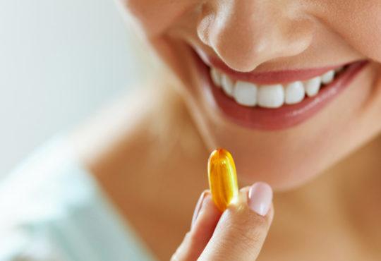 Nahaufnahme einer lachenden Frau, die ein Nahrungsergänzungsmittel in ihren Fingern hält