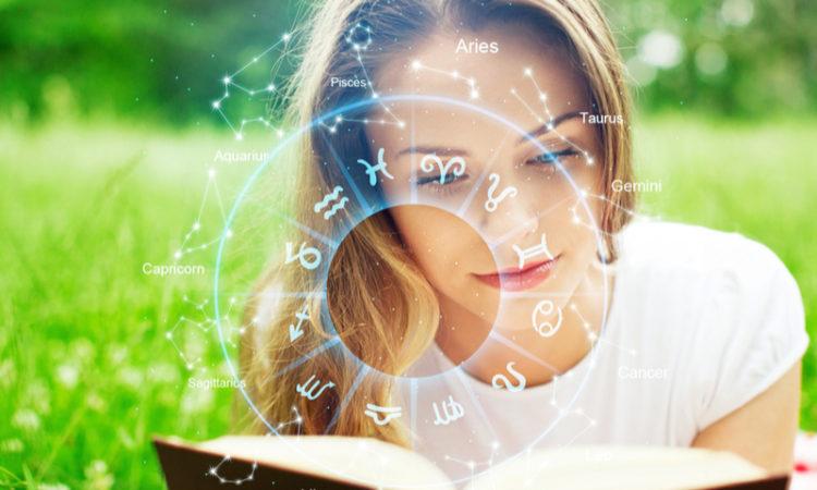 junge Frau liegt auf Wiese und liest Buch mit Horoskop