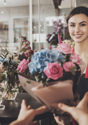 junge Floristin überreicht Blumenstrauß an Kunden