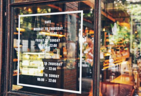 Fenster eines Cafes mit geplotteten Aufklebern mit Öffnungszeiten