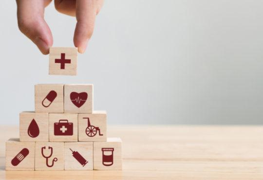 Hand stapelt Holzbausteine mit medizinischen Symbolen als Symbol für Krankenkassen zu einer Pyramide