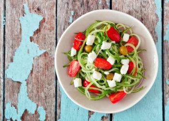 Schüssel mit Low Carb Zucchini Nudeln mit Tomaten und Käse auf Holzhintergrund