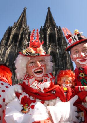 Jecken feiern als Clown verkleidet Karneval vor dem Kölner Dom
