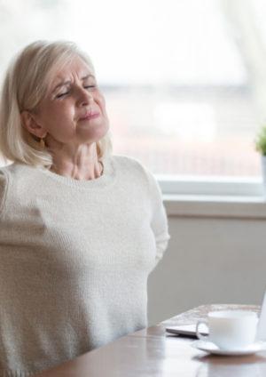 Ältere Frau sitzt am tisch und hält sich schmerzverzerrt den Rücken, da sie Probleme mit der Bandscheibe hat