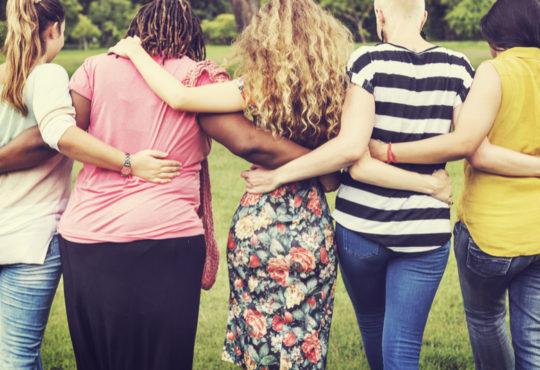 Rückansicht einer Gruppe von Frauen die sich in den Armen liegen als Symbol für den Weltfrauentag