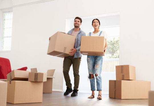 Junges, lachendes Paar mit Umzugskartons in neuer Wohnung