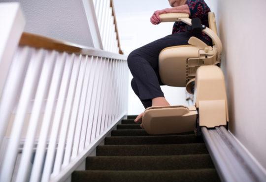 Seniorin fährt auf Treppenlift die Treppe hoch