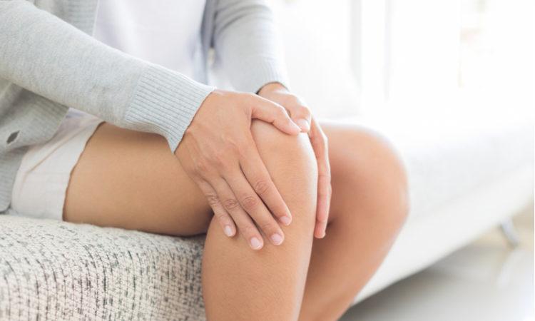 FRau sitzt auf der Couch und hält sich das Knie aufgrund von Knieschmerzen