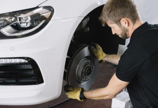 Mechaniker wechselt Bremsscheiben in Werkstatt