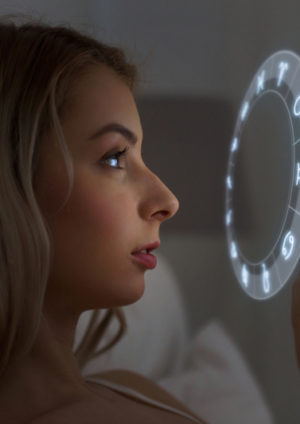 junge FRau checkt Horoskop nauf ihrem Handy