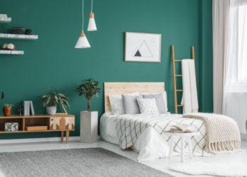 Modernes Schlafzimmer mit grüner Wand und mordernem, hellem Bett