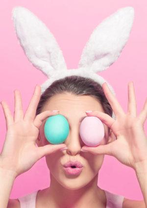 Junge Frau mit Osterhasenohren vor pinkem Hintergrund, die sich 2 bunte Ostereier vor die Augen hält