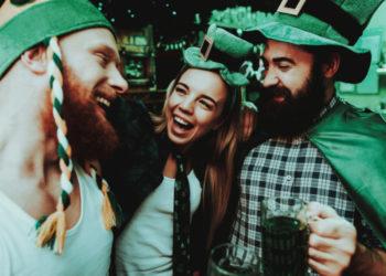 junge Leute tragen grüne Kleidung am St. Patrick's Tag, lachen und trinken