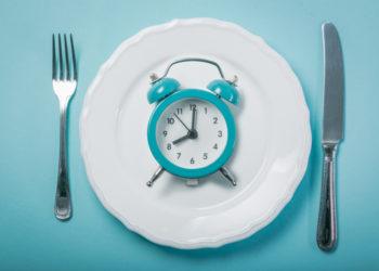 Wecker auf weißem Teller mit Messer und Gabel als Symbol für Intervallfasten