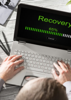 Mann sitzt an Laptop, auf dem Daten mit Datarecovery gerettet werden