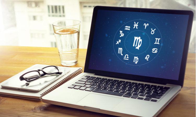 Laptop auf dem Sternzeichen abgebildet sind neben Wasserglas, Brille und Block
