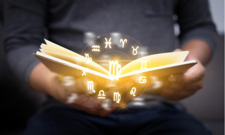 aufgeschlagenes Buch mit goldenen Tierkreiszeichen