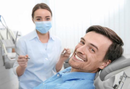 Mann liegt lächelnd auf Zahnarztstuhl