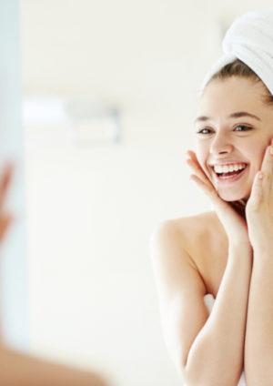 junge Frau in Handtuch und Turban schaut sich lachend im Spiegel an nach Gesichtskosmetik