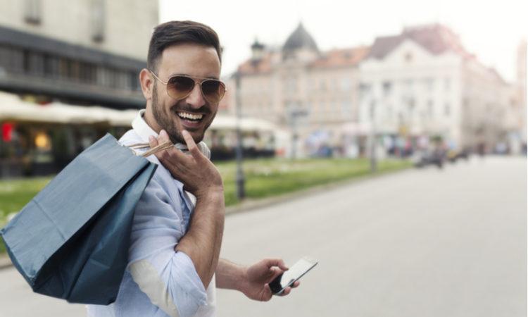 Stylisher junger Mann mit Sonnenbrille und Hemd trägt lachend eine Einkaufstüte über der Schulter