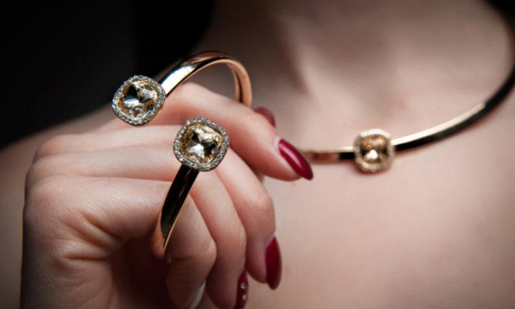 Frauenhand mit schönem Armband und Halskette im Hintergrund