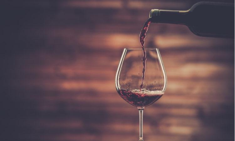 Glas Rotwein vor Holzhintergrung, in das gerade Wein eingegeossen wird